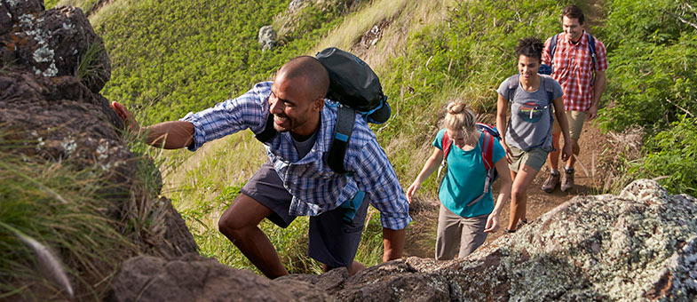 Group of friends climbing a mountain trail.