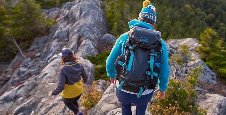 Two women hiking down a mountain trail.