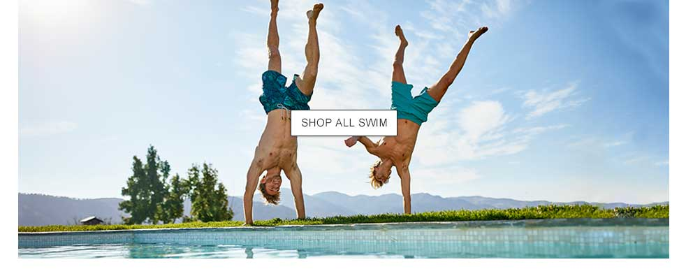 Two men doing handstands by the pool.