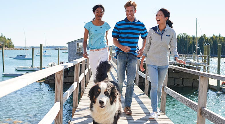 Friends walking on a dock with their dog.