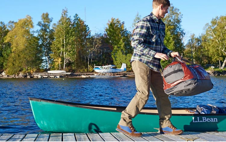 Man walking on dock with Adventure Pro Duffle from L.L.Bean
