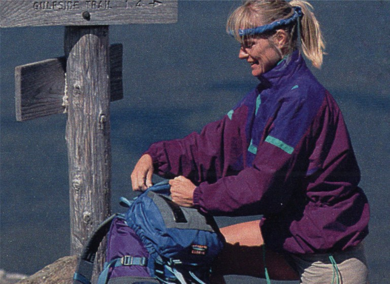 Woman in anorak adjusting her backpack by a trail sign.