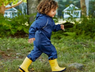 A happy toddler walking outside in a rain suit and yellow puddle boots.