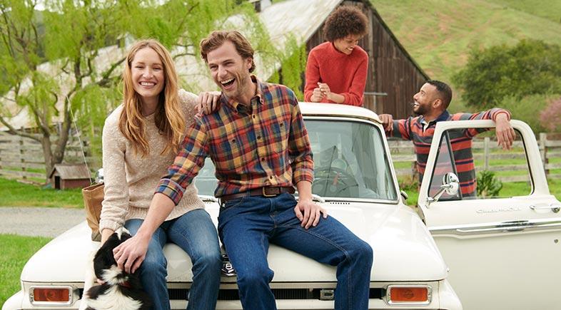 Friends sitting on a car.