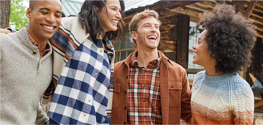 Four friends wearing L.L.Bean clothing outside talking and laughing.