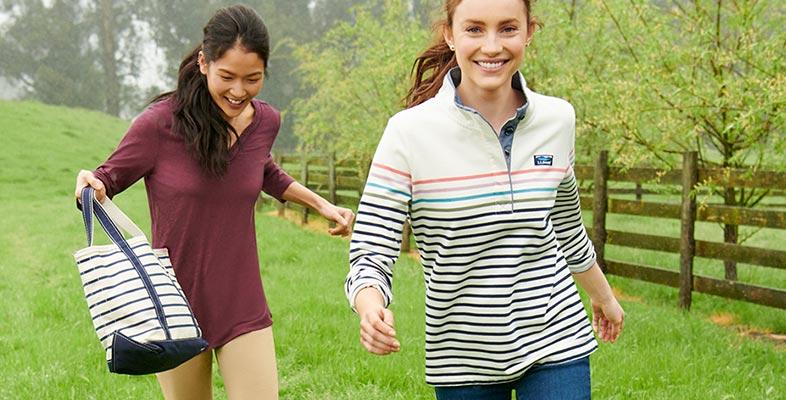 Two women wearing L.L.Bean clothing walking in a field.