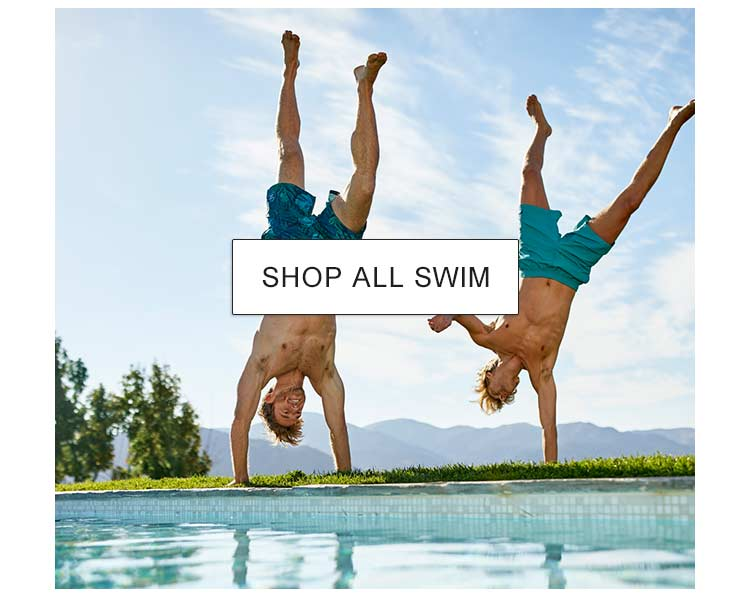 Two men doing handstands by a pool.